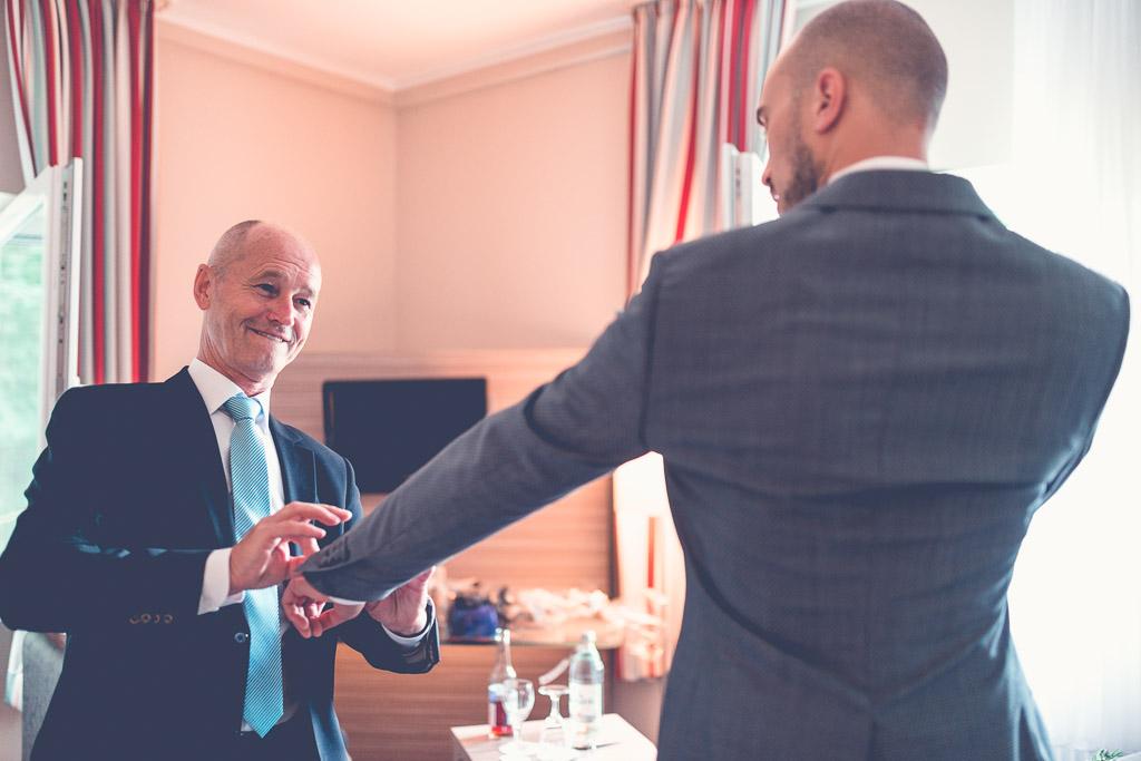 Hochzeitsfotograf in Berlin - Vater hilft Bräutigam mit grauem Anzug im Hotelzimmer