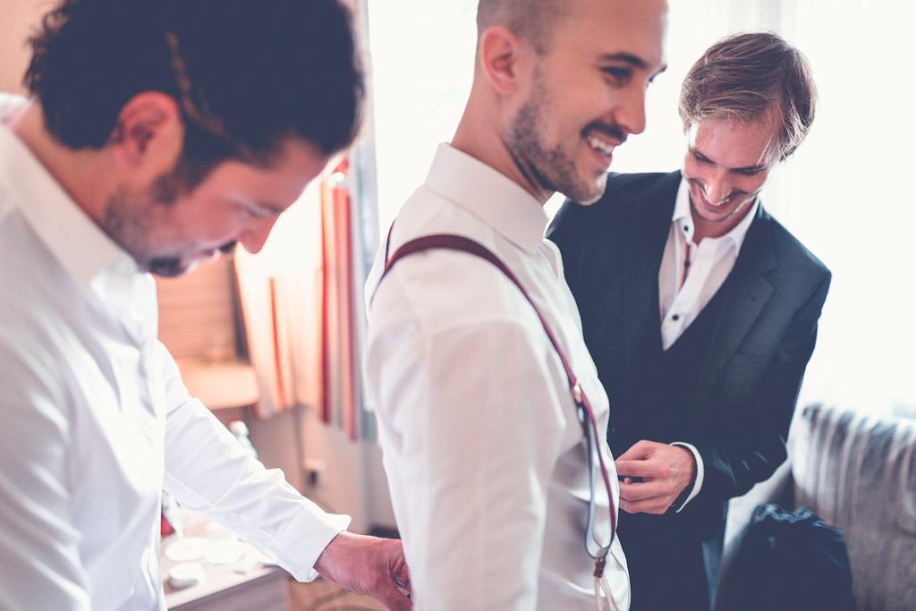 Hochzeitsfotograf in Berlin - Trauzeuge und Bruder helfen Bräutigam mit Hosenträgern