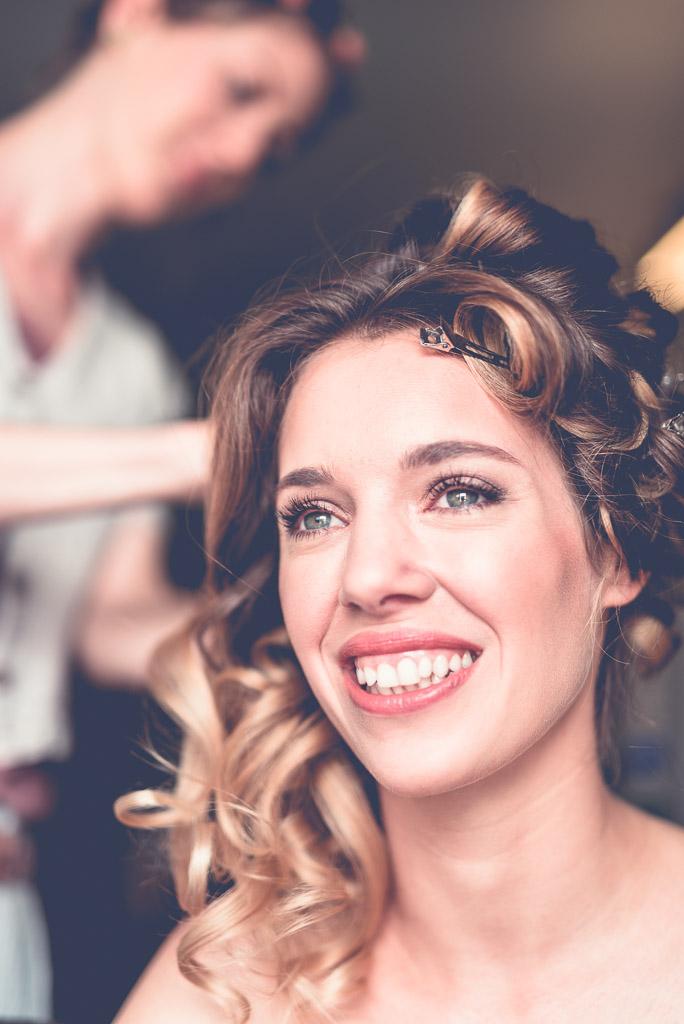 Berlin Hochzeitsfotograf Haare werden gestyled mit Sonne im lachenden Gesicht