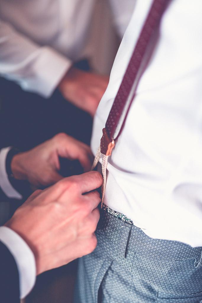 Hochzeitsfotograf in Berlin - Trauzeuge hilft Bräutigam mit Hosenträgern