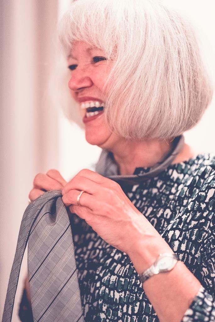 Berlin Hochzeitsfotograf Mama hilft beim Getting-Ready bindet Schlips und lacht