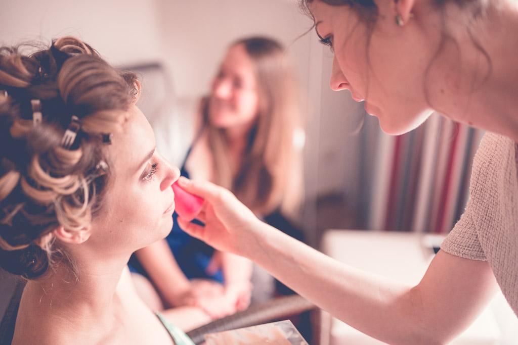 Berlin Hochzeitsfotograf Braut wird gepudert im Sonnenlicht