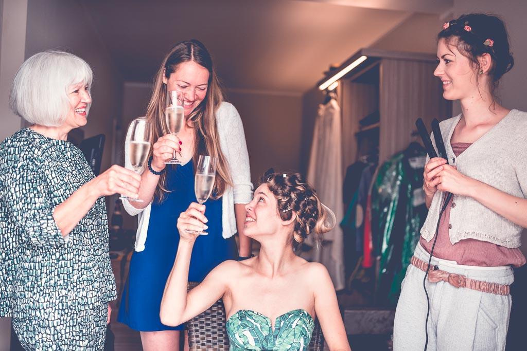 Berlin Hochzeitsfotograf Braut stößt an mit Sekt mit Mutter und Stylistin
